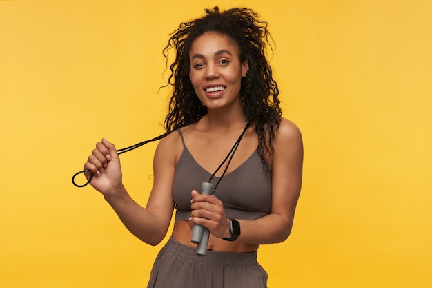 Portrait of cheerful beautiful young sportswoman standing and holding skipping rope on her neck isolated over yellow wall
