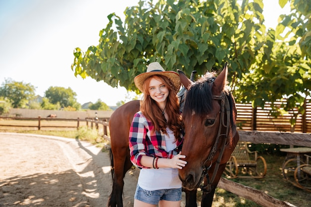 Portrait of cheerful beautiful young woman cowgirl with her horse