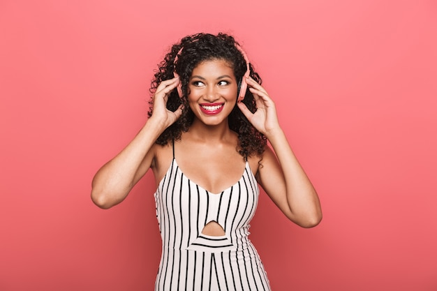 Portrait of a cheerful beautiful young woman wearing summer clothing standing isolated over pink wall, listening to music with wireless earphones, dancing