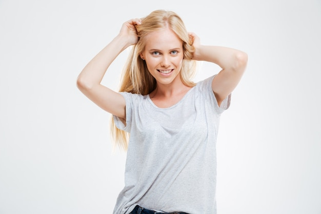 Portrait of cheerful beautiful young woman with blonde hair over white wall