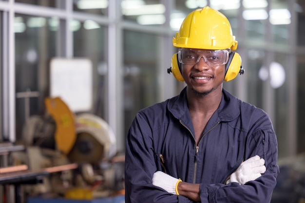 Portrait of cheerful black worker wearing protective headphones posing and enjoying work at background factory