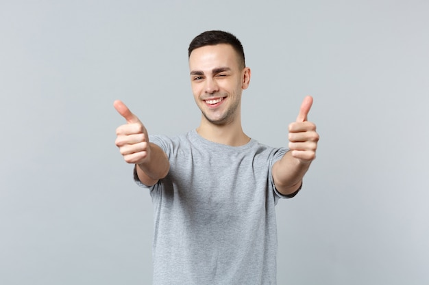Portrait of cheerful blinking young man in casual clothes standing and showing thumbs up