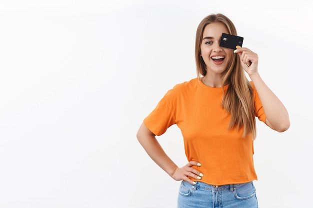 Ritratto di ragazza bionda allegra in maglietta arancione