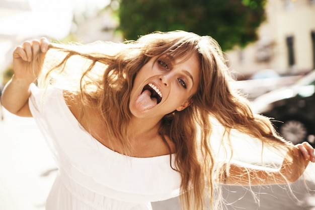 Portrait of cheerful blonde hipster girl without makeup  going crazy making funny face and showing her tongue on the street background. touching her hair