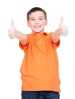 Il ritratto del ragazzo allegro che mostra i pollici aumenta il gesto - isolato sopra bianco.