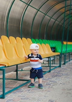 Portrait of a cheerful boy on a summer day. beautiful child in a baseball cap at the stadium near the bright seats.