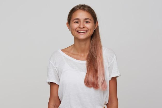 Ritratto di allegra giovane femmina dagli occhi marroni con capelli lunghi castano chiaro che guarda positivamente e sorride piacevolmente, vestita con una maglietta bianca di base mentre posa sul muro bianco