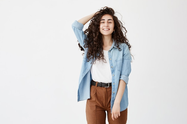 Portrait of cheerful brunette with long wavy hair, dressed in denim shirt and brown trousers, glad to recieve good news, student girl smiles broadly, rejoices life, expresses positive emotions