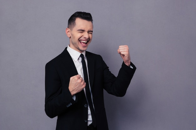 Portrait of a cheerful businessman celebrating his success over gray wall