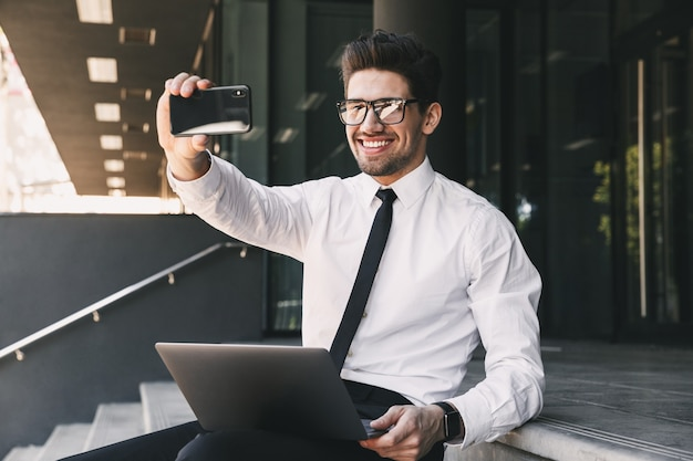 Portrait of cheerful businessman dressed in formal suit sitting outside glass building with laptop, and taking selfie photo on smartphone