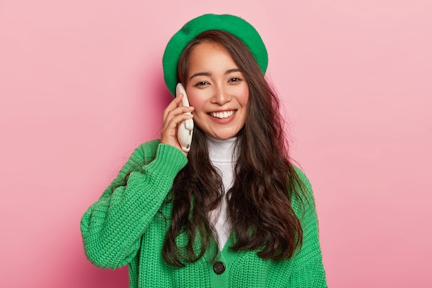 Portrait of cheerful carefree asian lady keeps mobile phone near ear, has telephone conversation, smiles positively, wears green beret