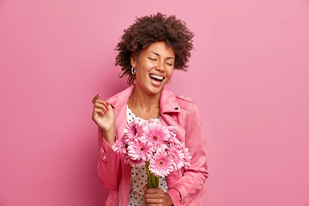 Portrait of cheerful carefree woman holds bunch of gerbera flowers expresses positive emotions closes eyes wears fashionable jacket isolated on pink wall