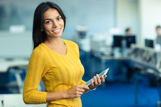 Portrait of a cheerful casual businesswoman in sweater standing with tablet computer in office