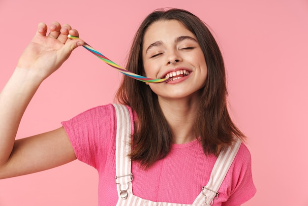 Portrait of cheerful charming girl smiling and eating multicolored marmalade isolated over pink wall