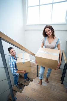 Portrait of cheerful couple holding cardboard boxes