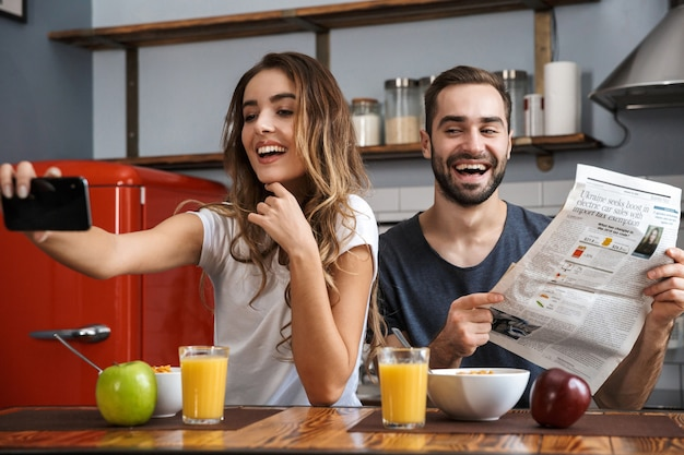 Portrait of cheerful couple man and woman taking selfie photo on cell phone while having breakfast in kitchen at home