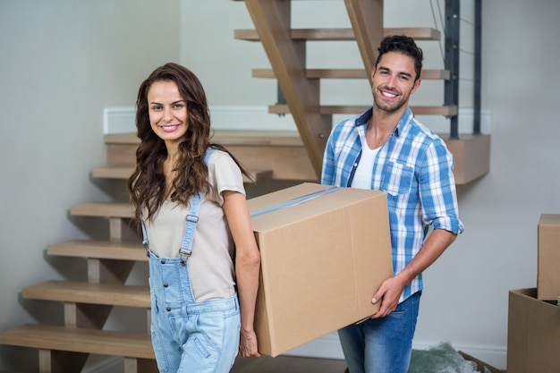 Portrait of cheerful couple with cardboard boxes