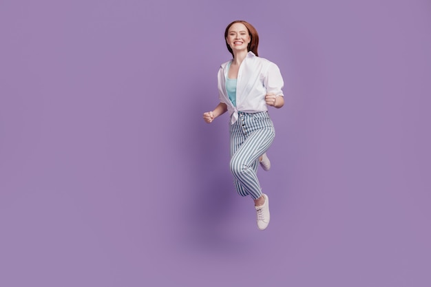 Portrait of cheerful crazy adorable lady jump run fast on violet background