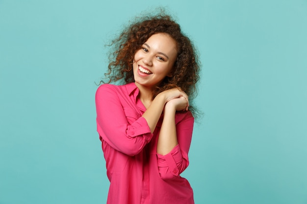 Portrait of cheerful cute african girl in pink casual clothes holding hands folded isolated on blue turquoise wall background in studio. people sincere emotions, lifestyle concept. mock up copy space.