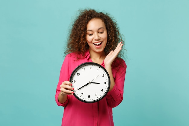 Portrait of cheerful cute african girl in pink casual clothes holding round clock isolated on blue turquoise wall background in studio. people sincere emotions, lifestyle concept. mock up copy space.