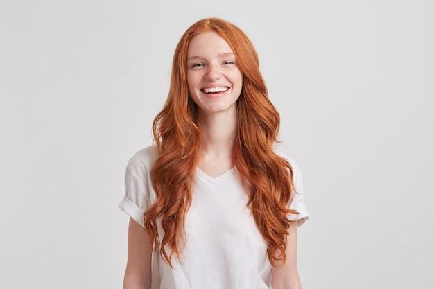 Ritratto di giovane donna allegra carina rossa con lunghi capelli ondulati