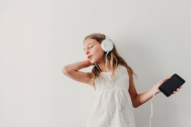 Portrait of a cheerful cute teenager girl listening music in mobile phone and headphones. dancing at home.