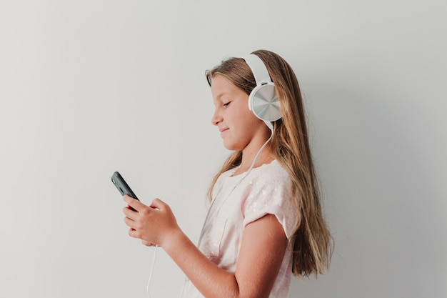 Portrait of a cheerful cute teenager girl listening music in mobile phone and headphones.
