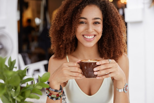 Portrait of cheerful dark skinned female with bushy afro haistyle, holds cup of coffee or latte, sits against cafeteria interior, being in good mood