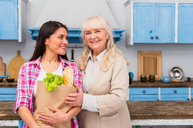 Portrait of cheerful daughter and her senior mother standing in the kitchen