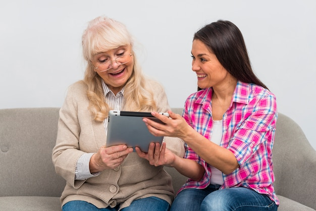 Portrait of cheerful daughter showing digital tablet to her senior mother