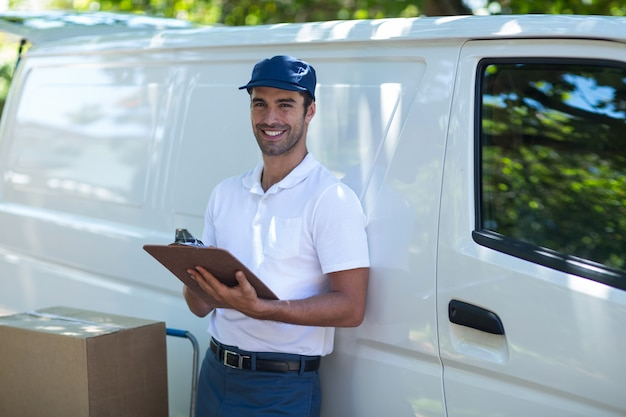 Portrait of cheerful delivery man writing in clipboard