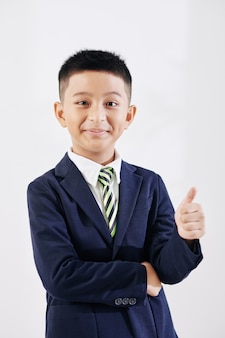 Portrait of cheerful diligent vietnamese schoolboy showing thumbs-up and smiling