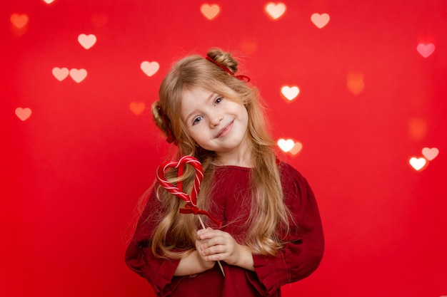 Portrait of a cheerful dreamy little girl with a heart shaped candy in her hands isolated on a red background