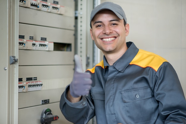 Portrait of a cheerful electrician giving thumbs up