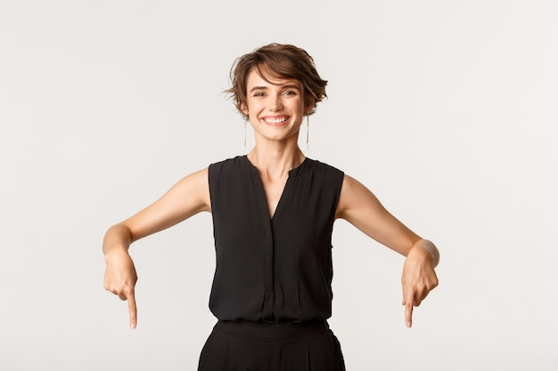 Portrait of cheerful elegant woman showing banner, smiling happy and pointing fingers down.