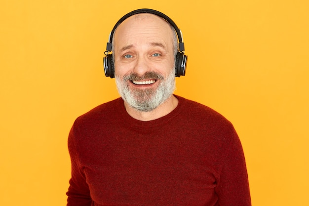 Portrait of cheerful emotional senior man with thick gray beard posing isolated using wireless headphones