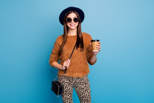 Portrait of cheerful emotions girl have fall spring holiday hold paper card cup coffee beverage latte enjoy wear handbag good look brown clothes isolated blue color wall
