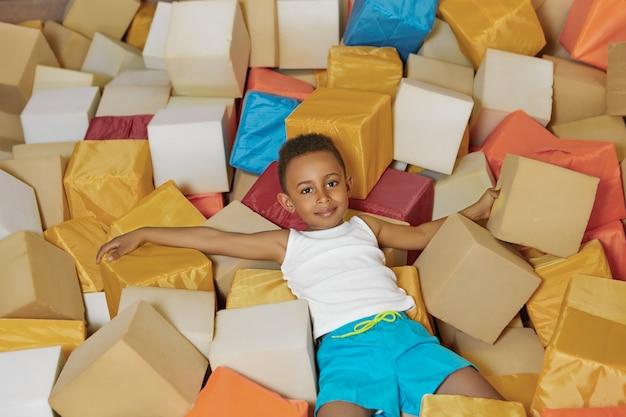 Ritratto del ragazzino afroamericano allegro energico che gioca con i cubi molli nella piscina asciutta