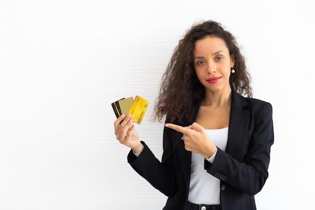 세로 쾌활한 흥분된 라틴 비즈니스 여자 곱슬 머리 모델 손에 신용 카드를 들고.