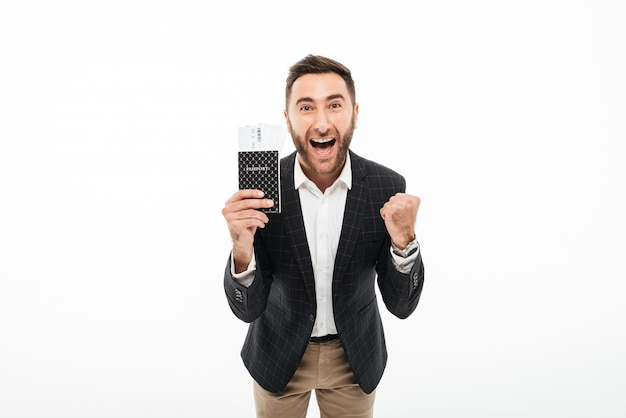 Portrait of a cheerful excited man holding passport