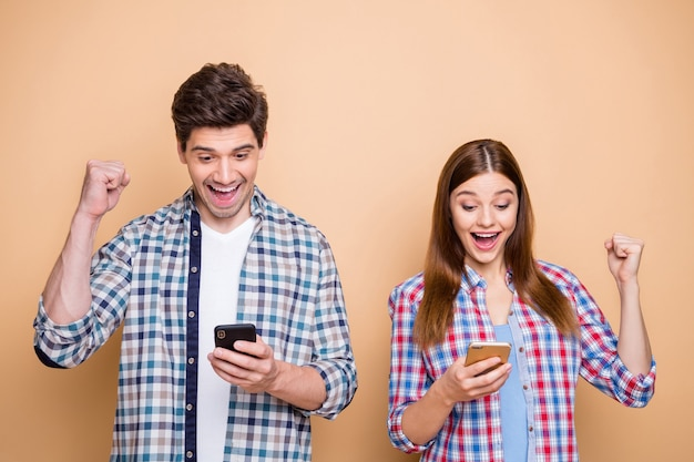 Portrait of cheerful excited married two people use smartphone get social media notification about winning lottery scream wow yes raise fists wear plaid shirt isolated over pastel color background