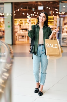 Portrait of cheerful excited young woman in casual outfit using credit card and getting rewarded for making purchases in mall