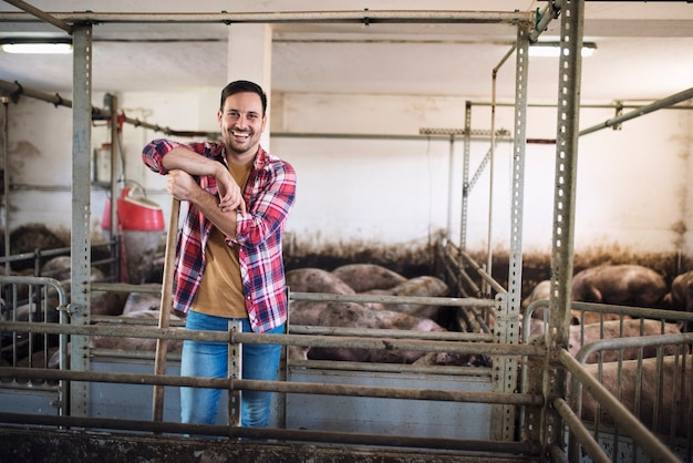Ritratto di allegro contadino in piedi nella stalla di allevamento di suini
