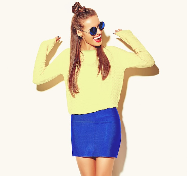 Portrait of cheerful fashion hipster girl going crazy  in casual colorful hipster yellow summer clothes with red lips