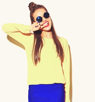 Portrait of cheerful fashion smiling hipster girl going crazy in casual colorful yellow summer clothes with red lips isolated on white biting her finger