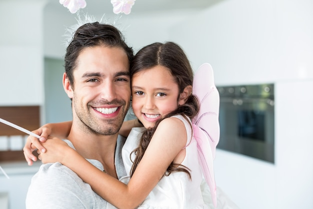 Portrait of cheerful father carrying daughter in fairy costume