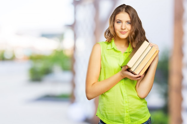 Portrait of a cheerful female teenager with a  book