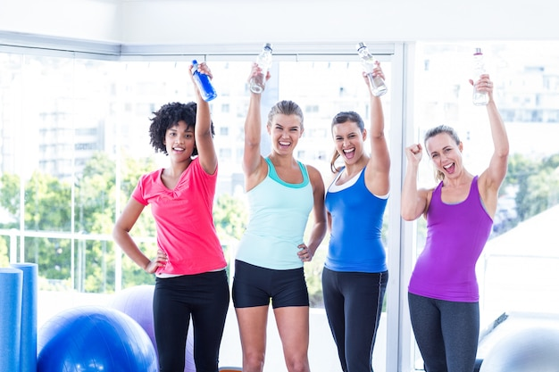 Portrait of cheerful fit women with water bottles