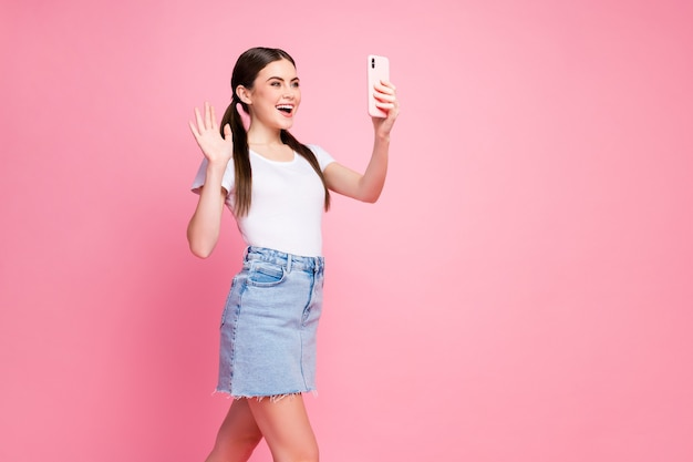 Portrait of cheerful friendly girl taking selfie making video call wave hand