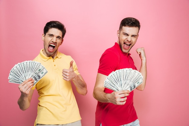 Portrait of a cheerful friends holding money